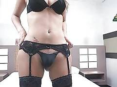 Tgirl in sexy black underwear and stockings is posing for camera.