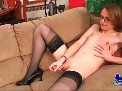 Slutty shemale in glasses is masturbating on the sofa
